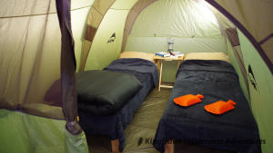 The tents provide standing room for most guests (1.9 metres tall) and are outfitted with wooden beds with the thickest and widest Therm-a-rest mattresses available. Sheets, fleece blankets, full-size pillows, warm barrel-style sleeping bags, and hot water bottles are all provided to ensure a good night's sleep.