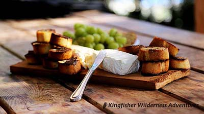 An appetizer of baked brie, grapes and toasted baguette.